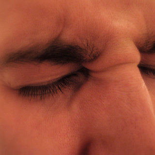 Photographic closeup of a man's squinting face, implying a severe headache.