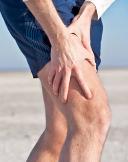 Photo of man in shorts holding knee, presumably because it hurts.