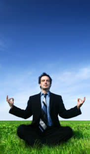 Typical stock photo of a guy in a suit meditating, sitting cross-legged in a field with a blue sky background, representing the common belief back pain might be helped by meditating and/or yoga and stress relief in general.