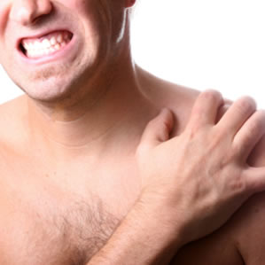 Photograph representing pain. It's a picture of a man cropped to show just his face, chest, and left shoulder. He's grimacing and clutching his shoulder with the opposite hand. DOMS doesn't usually hurt quite that much, fortunately.