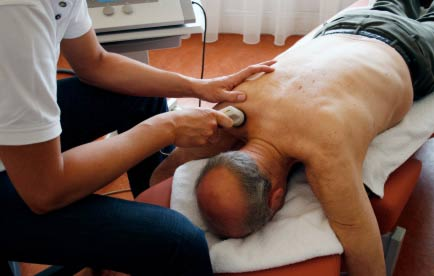 Photograph of an elderly man lying face down on a therapy table, with a professional applying ultrasound to his back.